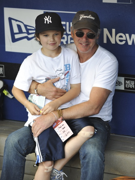 Richard Gere and son Homer James sit in the New York Yankees dugout prior to their game against the New York Mets at Citi Field in Flushing, NY