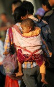 A mom carries her baby while heading to her ship at Xiuyinggang Port, China