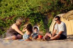 A nanny plays in the sand with Adam and daughters Sunny and Sadie