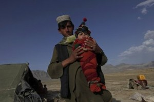 A Kuchi tribal man carries a six-month-old baby traditionally wrapped up