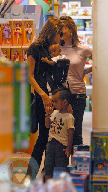 Angelina Jolie wearing daughter Zahara while holding Maddox