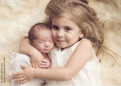 Big Sister Ella cuddles Baby Leo