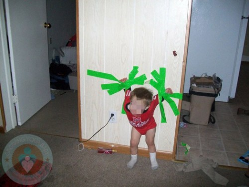 distressed toddler fixed to wall