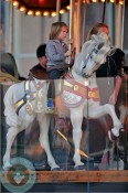 River Deary rides the carousel in Brooklyn