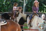 Isla Fisher with daughters Elula and Olive riding the ponies