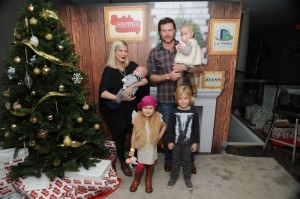 Tori Spelling, Dean McDermott, and Liam, Stella, Hattie and Finn pose by the Xmas tree