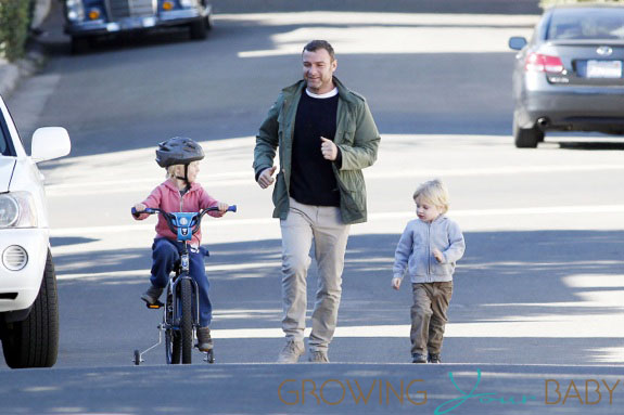 Liev Schreiber and little Samuel cheer on Alexander as he tests out his training wheels in Los Angeles