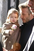 David Beckham holds onto his daughter Harper as they head to a waiting car after watching Victoria Beckham's Fall 2013 fashion show