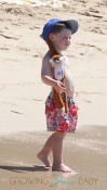 Coleen Rooneys' son Kai sports a monkey attached to his hat while at the beach