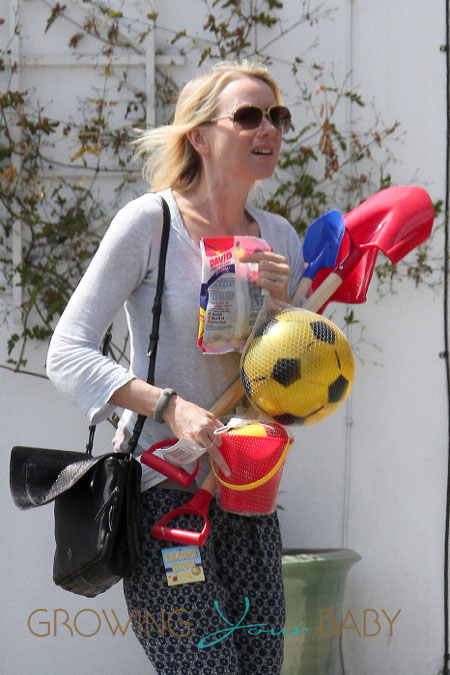 Naomi Watts has her hands full with toys while out shopping in Los Angeles