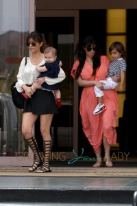 Kim and Kourtney carry the kids to the car