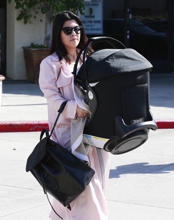 Kourtney Kardashian leaves a dance class carry an Orbit Baby Car seat