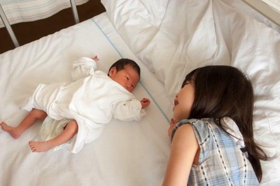 little girl meeting sibling