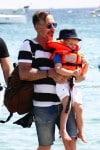 David Furnish carries son Elijah in St