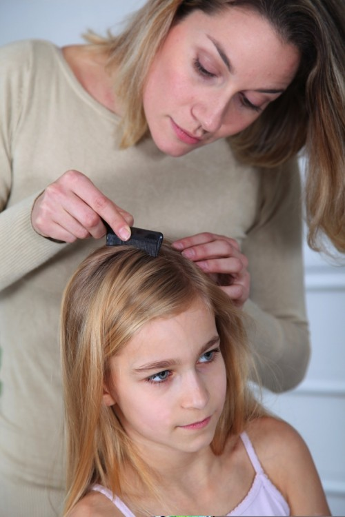 mom checks daughters hair for lice