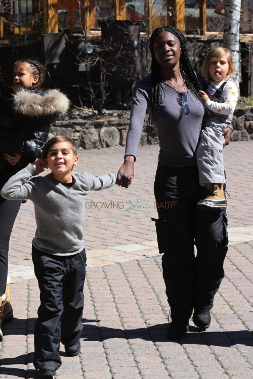A nanny carries Penelope Disck with out in Vail with Mason Disick and North West