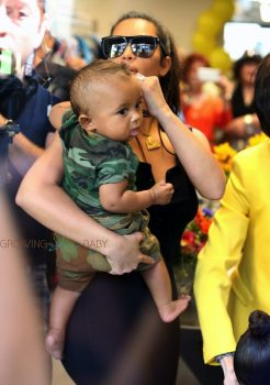 Kim Kardashian carries son Saint West at her grandmother's store opening in San Diego