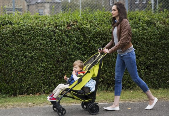 mom pushing child stroller