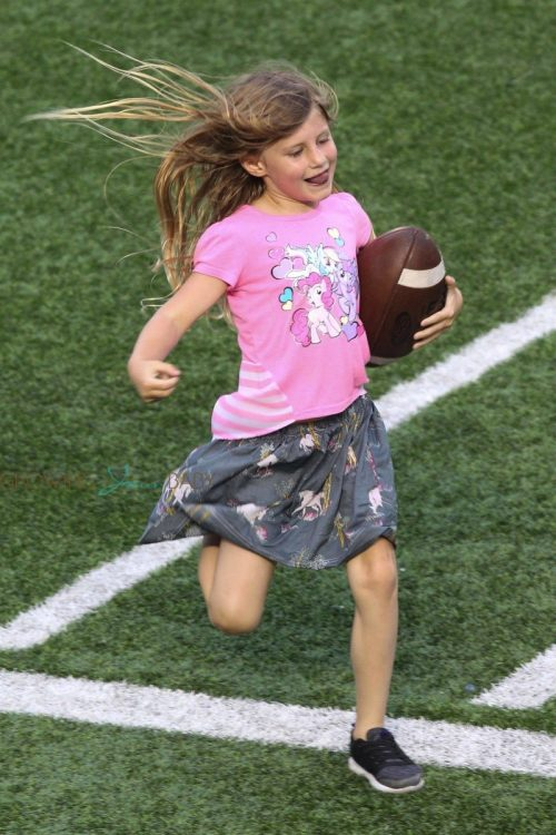 Vivian Brady running the ball at dad Tom Brady's Best Buddies Charity Event