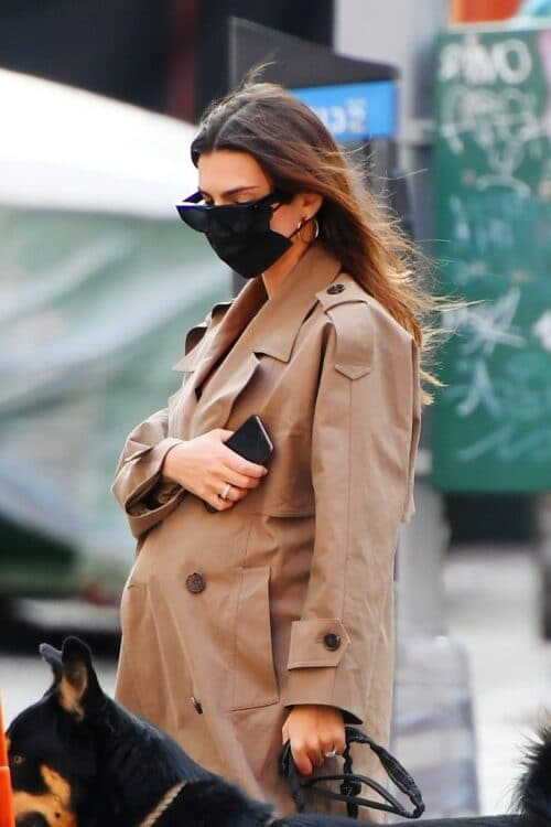 Emily Ratajkowski looks stylish in a trench coat as she shows off her growing baby bump