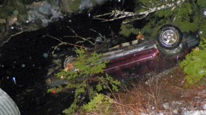 An SUV rests upside down in water alongside Route 6 in Kossuth Township, Maine