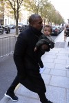 Kanye West carries daughter North West into a Paris hotel