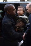 Kanye West carries daughter North into a Paris hotel