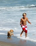 Kingston Rossdale runs on the beach with his puppy