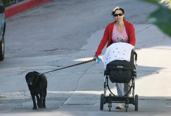 Multitasking new mommy Minnie Driver takes both her baby Henry and dog for a walk