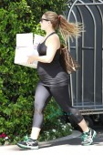 Cacee Cobb shows off her growing baby bump in a black tank top and workout leggings as she carries a package into the Bel-Air Hotel in Los Angeles