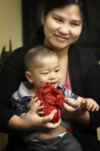 Roland Lian Cung Bawi 14 months holds a 3D model of his heart