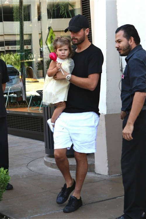 Scott Disick carries daughter Penelope out of an American Girl Party