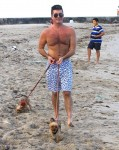 Simon Cowell walks his dogs on the beach in Miami