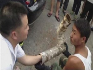 Rescuers try to reach the trapped infant inside the cut away sewage pipe in Jinhua City, Zhejiang Province